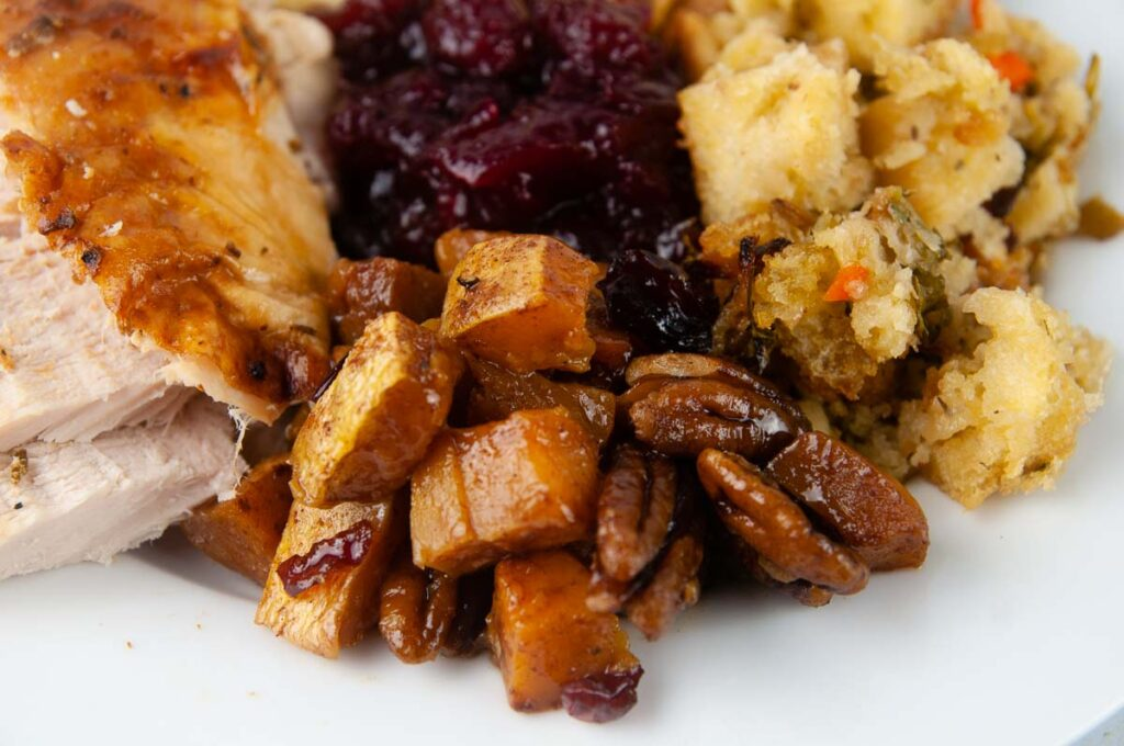A plate of a turkey dinner featuring turkey breast, cranberry sauce, stuffing and roasted butternut squash.