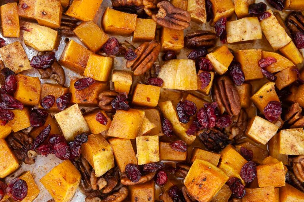 A tray of cinnamon sugar butternut squash out of the oven and tossed with cinnamon, brown sugar and craisins