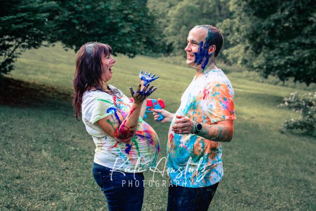 a pregnant woman and her husband covered in rainbow paint